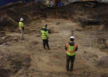 SKANSKA-Trident staff inspect graves exposed on February 13, 2013.